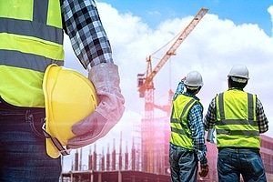 three men standing at a construction site conducting regular site audits