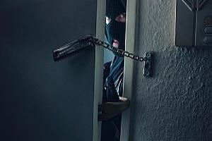 a burglar peeking through a crack in a door of a business he is breaking in to