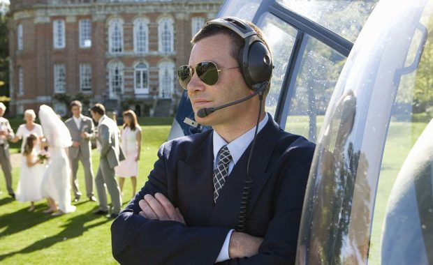 An event security guard in sunglasses by a helicopter during wedding event