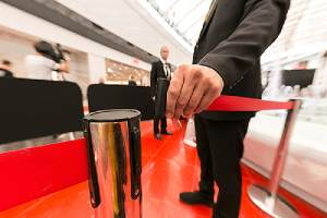 An event security personal fastens a red tape. The cost to hire security for an event varies depending on the types of event