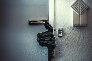 Intruder's hand in an attempt to break in. Home Security Systems help deter criminal activities