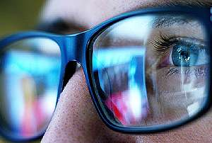 Security monitor reflected on eyeglasses. Modern home security systems enable homeowners to monitor live