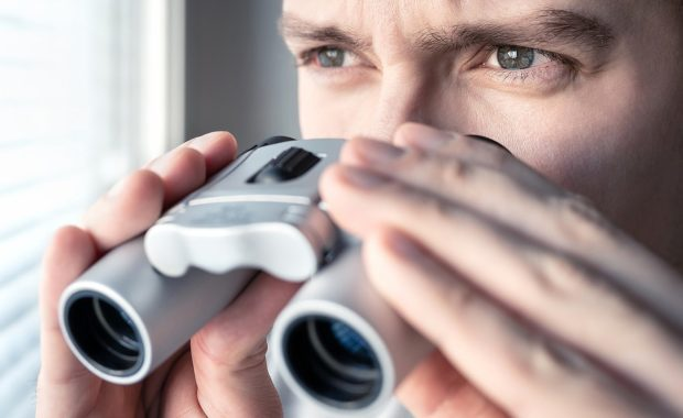 A private detective service agent with binoculars looking out the window