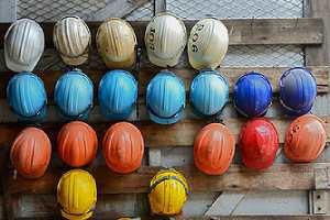 Rows of construction site safety helmets. Hiring of professional security guards can be beneficial in the workplace