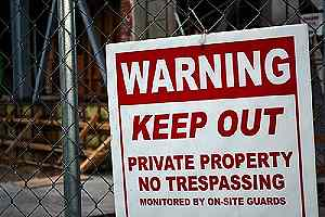 A signboard on a fence warning against trespassing. Armed security officers is enough to deter thieves