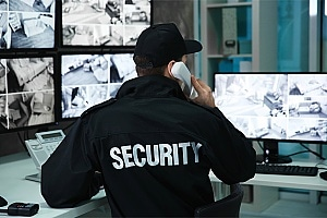 a uniformed security officer performing remote surveillance services