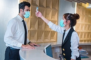 receptionist taking the temperature of an employee during a pandemic
