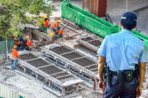 Construction Site Security Guard Watching Workers