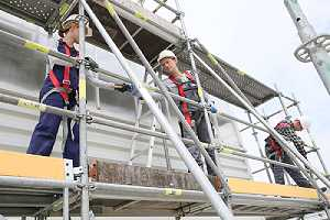 Construction workers installing scaffolding . Safety is of paramount importance in construction sites