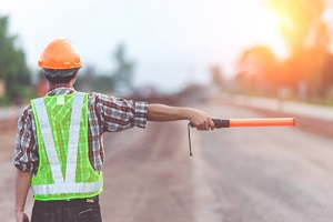 construction security guard with light stick on road construction background