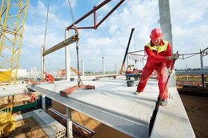 worker in safety protective equipment installing concrete floor slab