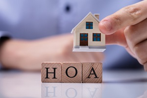 businessman hand placing house models on wooden HOA cubic blocks over desk