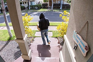 a thief stealing a package from a house that belongs to a homeowners association