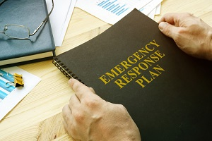 commercial property management worker open disaster and emergency response plan for reading