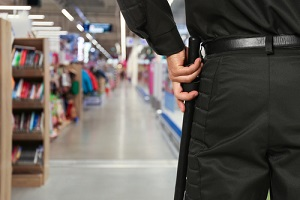 guard in uniform with police baton in shopping mall